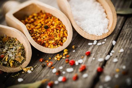 sal: mezclas de especias para cocinar pescado y pollo y la sal en cucharas de madera, hojas de laurel y granos de pimienta en la mesa de �poca antigua