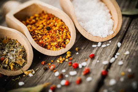 mineral salt: mixed spices for fish and chicken cooking and salt in wooden scoops, bay leaves and pepper corns on old vintage table