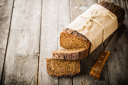 Traditional bread with seeds wrapped in paper on old wooden table photo
