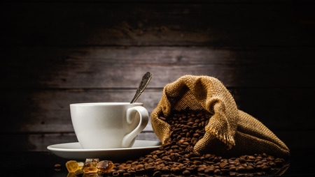 cup of coffee and bag in front of wooden background photo