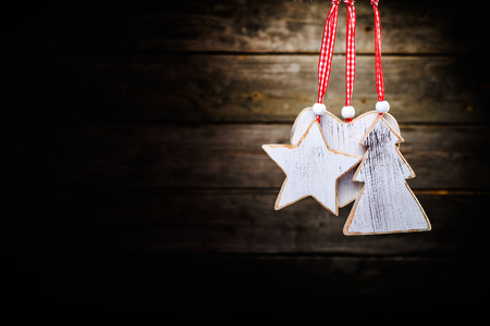 christmas wooden decorations - star, heat and christmas tree hanging on rope in front of wooden background photo