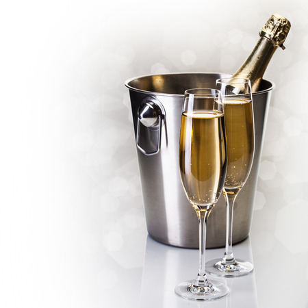 Champagne bottle in bucket with glasses of champagne in front of bokeh background