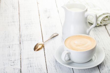 cup of cappuccino and jug of milk on old painted white wooden table.