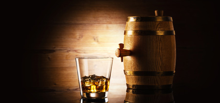 glass of whiskey with ice cubes and barrel in front of wooden background
