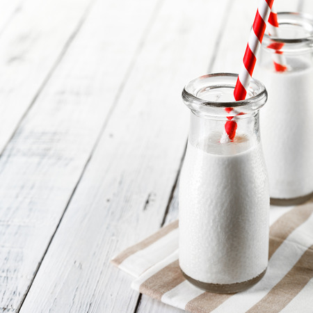 Two bottles with milk on lite wooden background with red striped straws