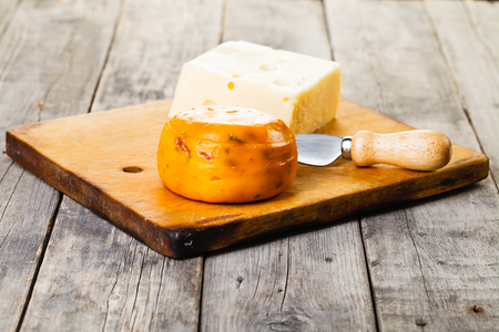two heads: Two heads of cheese on wooden board and knife