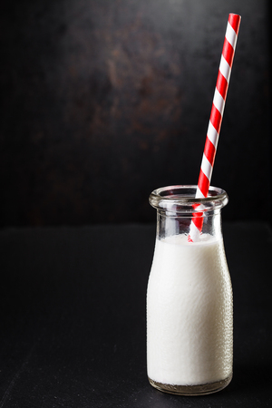 One bottle with milk on dark background with  striped straw Stock fotó