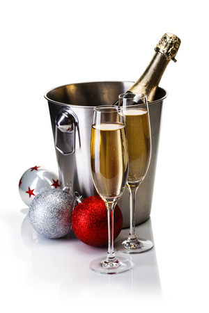 Champagne bottle in bucket with glasses of champagne and christmas balls isolated on white background