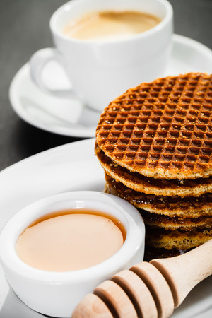 honey waffles and coffee on ceramic background