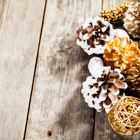Rustic natural wooden background with painted christmas pine cones Stock fotó