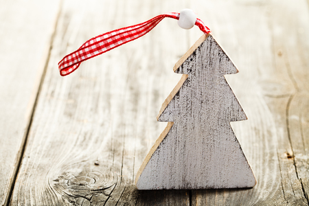 Christmas tree made of wood with rope standing on wooden background