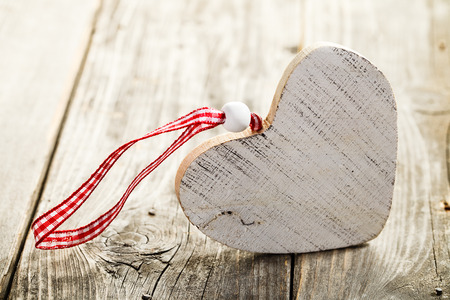 Christmas heart made of wood with rope standing on wooden background Standard-Bild