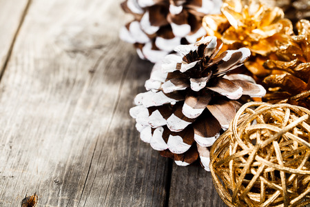 Rustic natural wooden background with painted christmas pine cones Standard-Bild