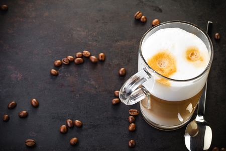 glass of latte ad spoon on dark rustic background