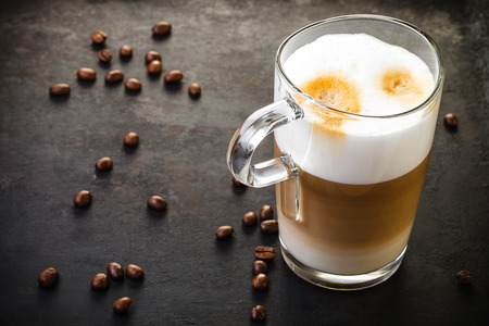 glass of latte on dark rustic background