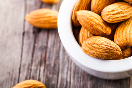 almonds in ceramic bowl on wooden background Stock fotó