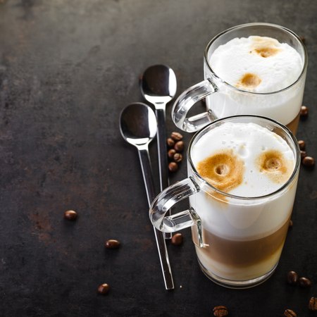two glasses of latte ad spoons on dark rustic background Stock fotó