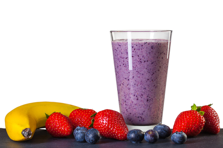 Smoothie made of blueberry, banana and strawberry in glass isolated on white background