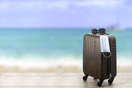 Concept of pandemic travel. Suitcase with protection mask on the beach
