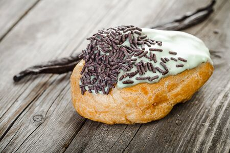 French pastry filled with vanilla cream, glaze with mint and chocolate chips  on old wooden table