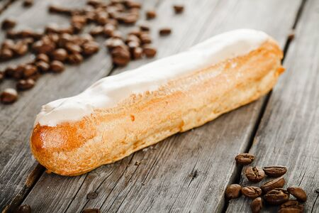 Tasty eclair with cream and coffe beans on old wooden table