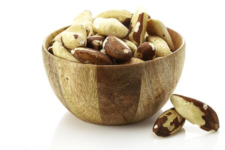 brazilian nuts in wooden bowl  isolated on white background Standard-Bild