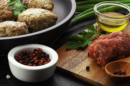 cutlets on pan, forcemeat and spices on board over old rustic background