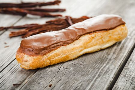 Tasty eclair with chocolate cream  on old wooden table