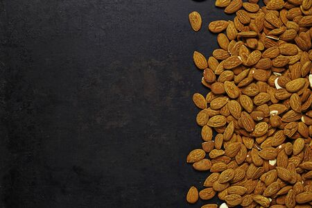 almonds lying on old rustic background. With place for copy