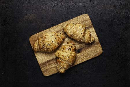 croissants on  on wooden board lying on old rustic background