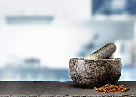 granite mortar and spices on table in front of blurred kitchen Standard-Bild