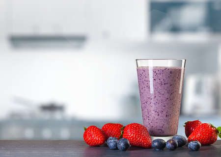 glass of smoothie and berries on table in front of blurred kitchen