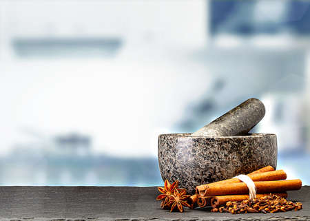granite mortar and spices on table in front of blurred kitchen