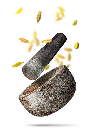 Granite mortar and cardamom seeds falling isolated on white background