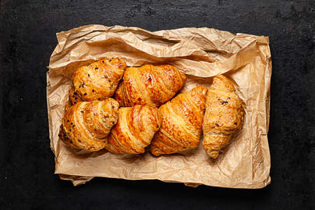 croissants on  crumpled baking paper lying on old rustic background Standard-Bild