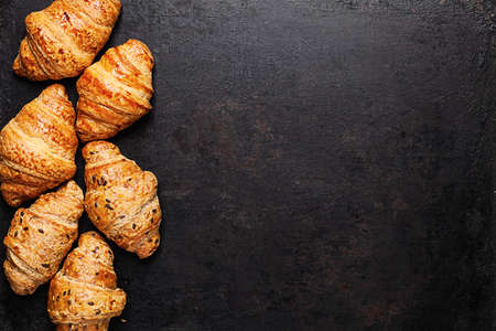 croissants lying by sides on old rustic background.