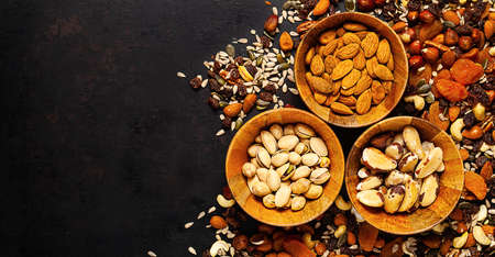 mix of different nuts and dried fruits in wooden bowl standing on rustic background Standard-Bild