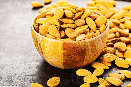 almond in wooden bowl standing on rustic background