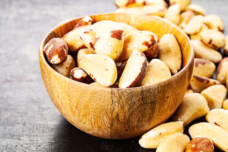 brazilian nuts in wooden bowl standing on rustic background