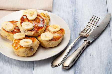 Homemade pancakes with raisins poured on with condensed milk and served with cutted bananas Standard-Bild