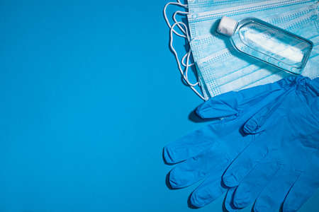 Medical gloves mask and alcohal gel for protecting infection during virus pandemic top view on light blue banner background with copy space