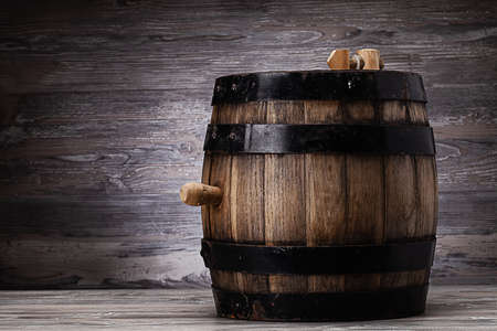 Old wooden barrel standing on table in old cellar Standard-Bild