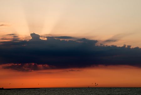 Setting sun behind clouds on the baltic sea