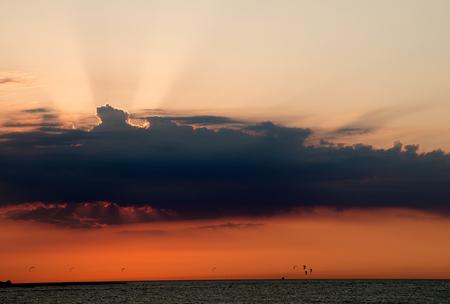 perish: Setting sun behind clouds on the baltic sea