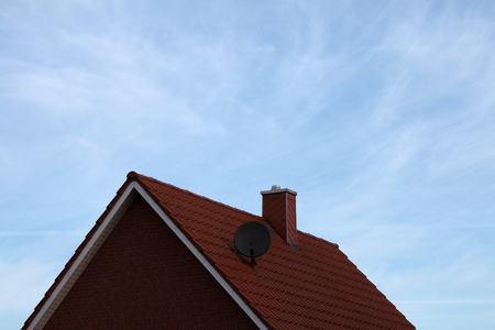 House roof with satellite dish and chimney, slightly cloudy sky