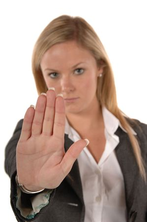Blond women in business clothing with hand up signaling STOP photo