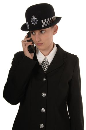 constable: Uniformed UK female police officer using her radio isolated on white Stock Photo