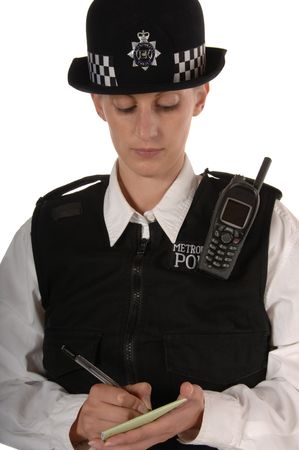 Uniformed UK female police officer writing in book