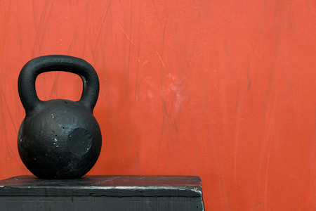 kettle bell: Black kettle bell on a black jump box, against a red wall