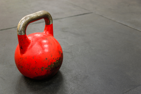 gym floor: Close-up of red kettlebell on black gym floor